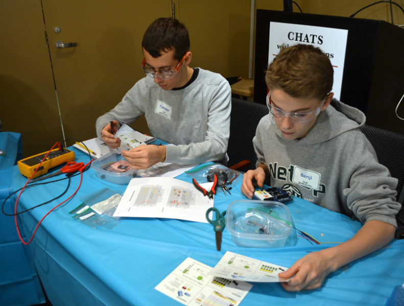Tanager Karchenes (left) and Benji Pugh assemble robots. (Maia Zewert photo)