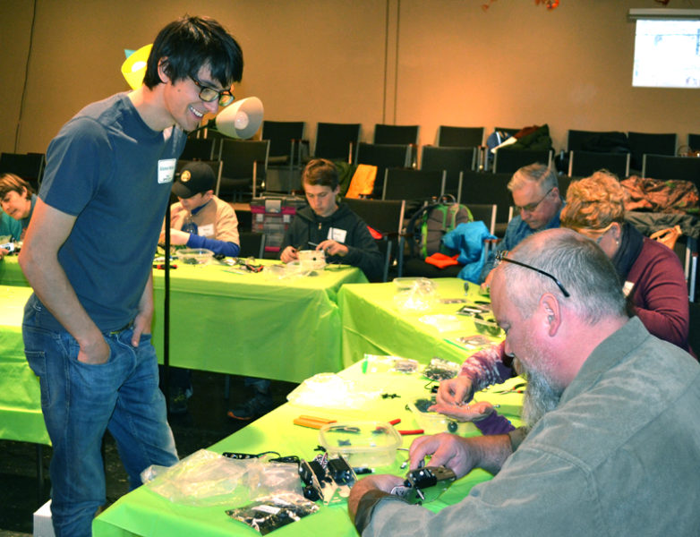 Mike Lee (left) looks on during the construction of robots at Skidompha Library in Damariscotta on Sunday, Nov. 20. Lee recently joined the library staff as gizmo educator and coordinator. (Maia Zewert photo)