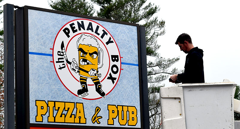 Dave Morgan, of The Sign Store & Flag Center in Auburn, works on the sign for The Penalty Box Pizza & Pub the morning of Tuesday, Nov. 15. The new restaurant in the 436 Main St. space formerly home to Romeo's Pizza will open at 5 p.m., Thursday, Nov. 17. (J.W. Oliver photo)