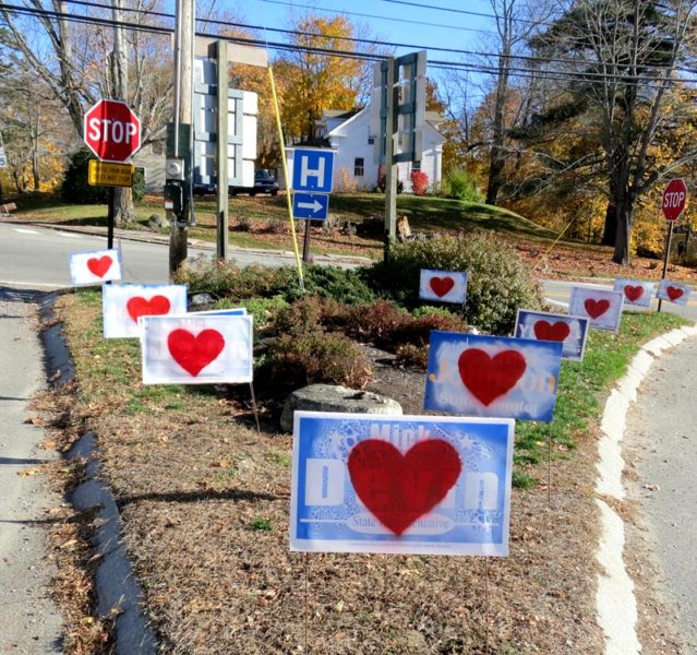 Campaign signs bearing hearts in the traffic island at the intersection of Academy Hill Road, Main Street, and Mills Road in Newcastle the morning of Thursday, Nov. 10. (Photo courtesy Chris Johnson)