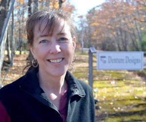 Kathryn A. Young stands in front of the sign for her practice, Denture Designs, at its new location at 40 Harrington Road in Walpole. Young will begin seeing patients at the new location Tuesday, Dec. 6. (Maia Zewert photo)