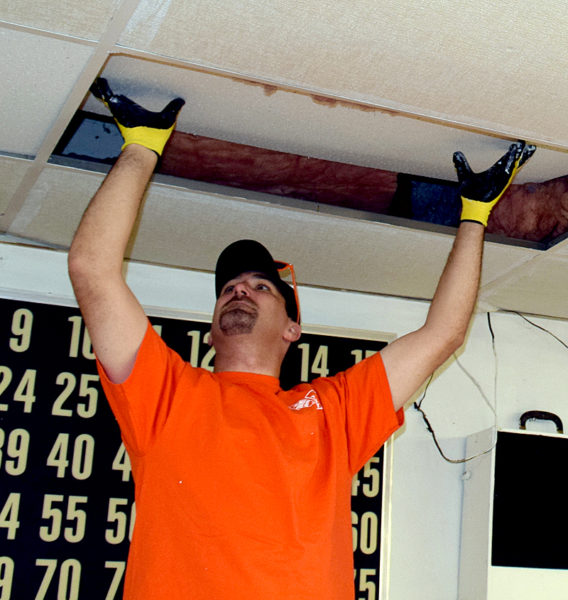 Jason Gray, a district sales manager for Home Depot Exteriors, replaces a ceiling tile at the American Legion post in Waldoboro. (J.W. Oliver photo)
