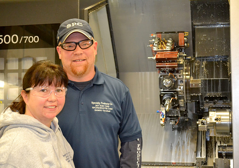 Mike and Paula Cuthbertson stand in front of one of the Specialty Products Co. machines Tuesday, Nov. 29. The Specialty Products Co. plant in Whitefield, which manufactures precision machine parts, will more than double in size in the next year. (Abigail Adams photo)