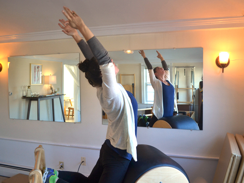 Phaelon O'Donnell demonstrates a Pilates exercise on a piece of equipment called the high barrel at her studio, Perch Pilates, in Wiscasset on Wednesday, Nov. 23. (Abigail Adams photo)