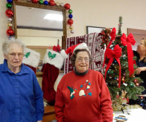 From left: Gwen Swank, Pam Meserve, and Mary Goulette prepare to deck the hall at the Alna Anchor Masonic Lodge.
