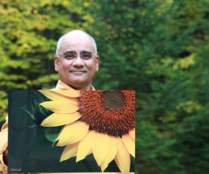 Dr. Rifat Zaidi holds a photo of a sunflower that will be on display at the Miles Campus of LincolnHealth from Saturday, Nov. 26 through Christmas Day. Zaidi's photographs are printed on aluminum, a much more durable medium than paper prints. All funds from the sale of the photographs will go toward building a school for girls in a deeply impoverished area in Pakistan.