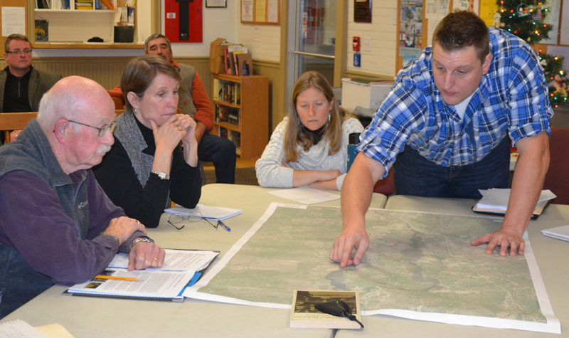 Wright-Pierce engineer Joe McLain points at a map as Bristol Dam Advisory Committee members (from left) Bill Benner, Abby Ingraham, and Claire Enterline look on during a committee meeting Wednesday, Dec. 7. (Maia Zewert photo)