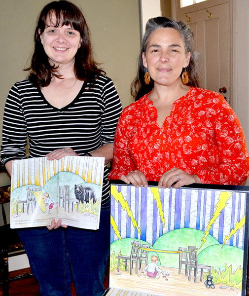 "Kate Kastelein (left) holds open a copy of ""Blankie's Diary"" as Crystal McLain displays one of her original illustrations for the book. (Maia Zewert photo)"