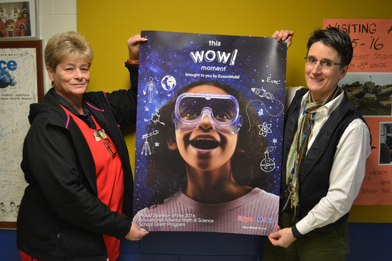 Mr. Mike's Market Manager Dixie Haley (left) and Great Salt Bay Community School Principal Kim Schaff hold an ExxonMobil poster promoting math and science. Haley applied for and recieved a $500 ExxonMobil Education Alliance grant for the school. (Maia Zewert photo)