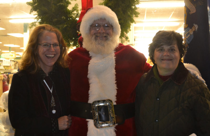 From left: Twin Villages Alliance Chair Mary Kate Reny, Santa Claus, and alliance board member Sarah Maurer celebrate the community and the season during the Wrap It Up street festival Thursday, Dec. 22. (Abigail Adams photo)