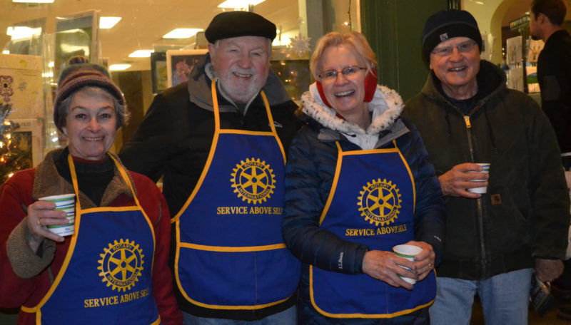 From left: Damariscotta-Newcastle Rotary Club members Linda Brunner, Bob Topper, Nancy Stoltz, and Bob Stephan sell nuts and candy to support area food pantries during the Wrap It Up street festival in Damariscotta on Thursday, Dec. 22. (Abigail Adams photo)