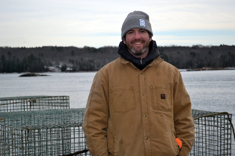 Ryan McPherson, the new owner of Glidden Point Oyster Sea Farm, stands on the dock of 637 River Road, the new headquarters for the business, on Tuesday, Dec. 20. (Abigail Adams photo)