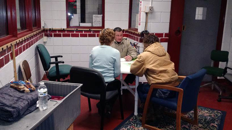 """Deputy James Read of the Lincoln County Sheriff's Office demonstrates a mock intake interview with Bridges to Treatment materials and a """"comfort kit"""" -- food, water, and blankets for participants."""