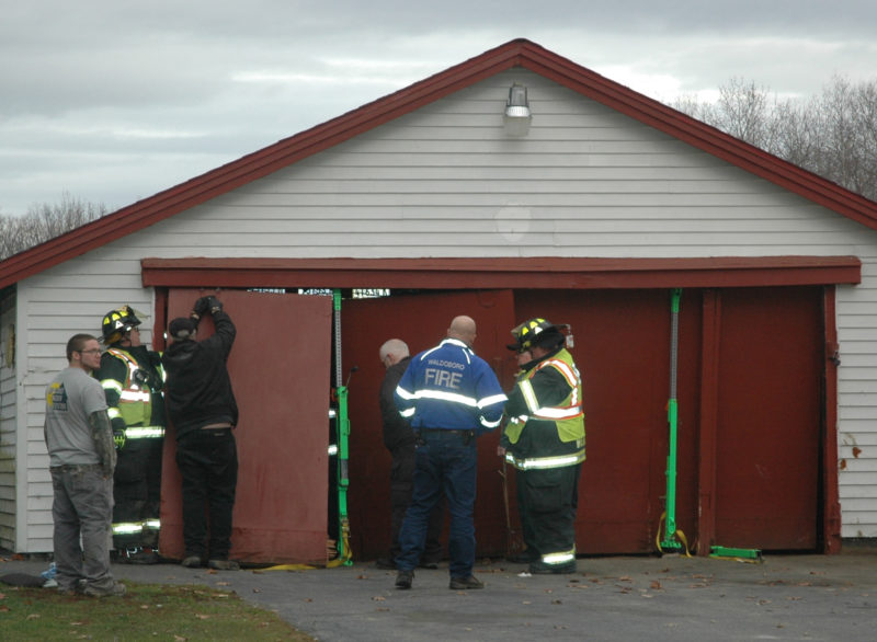 Firefighters use emergency jacks to ensure the stability of a garage during the extrication of an SUV that crashed through the garage on Upper East Pond Road in Nobleboro the afternoon of Friday, Dec. 2. (Alexander Violo photo)