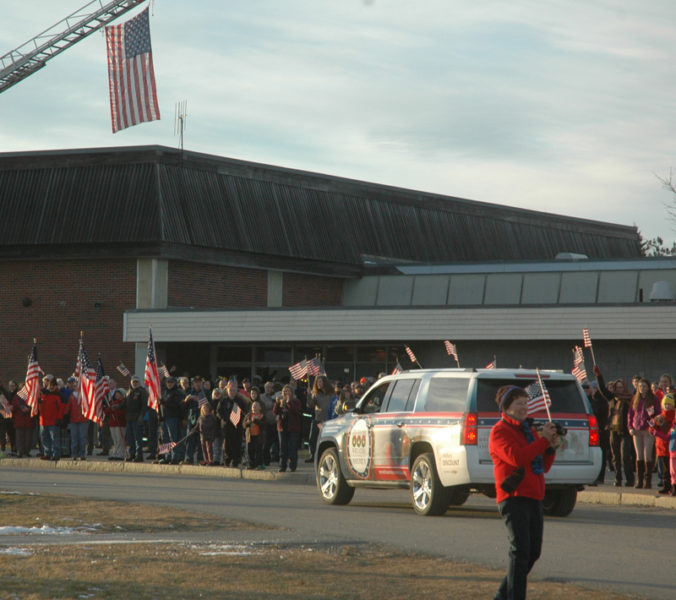 A crowd of people waving flags welcomes the Wreaths Across America convoy to Medomak Valley High School. (Alexander Violo photo)