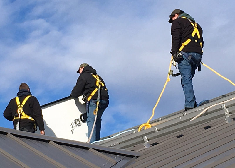 Workers install a solar array on the roof of the Whitefield municipal fire station in mid-December. (Photo courtesy Richard Simon)