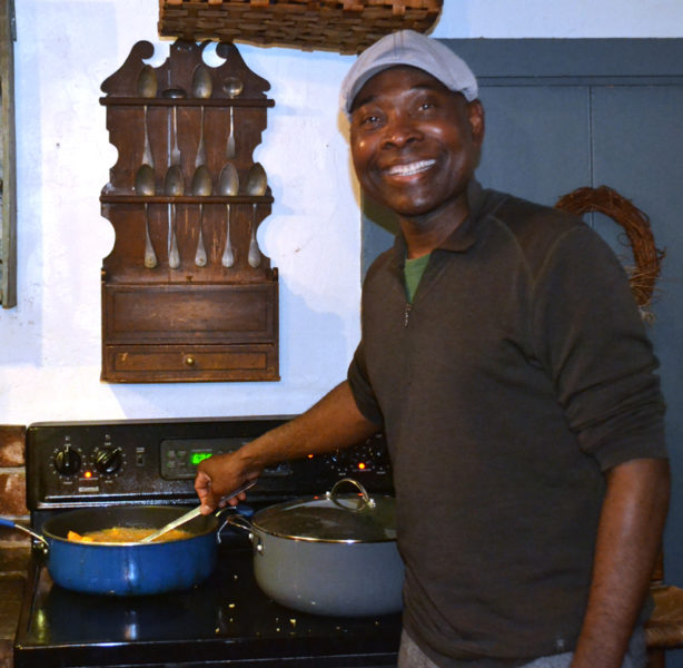 Messan Jordan Benissan prepares sweet potatoes, cooked in traditional Togolese fashion, for a community dinner at Patricia Stauble Antiques in Wiscasset on Thursday, Dec. 8. (Abigail Adams photo)
