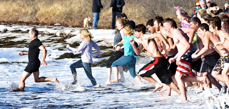 Participants in the eighth annual Pemaquid Polar Bear Dip race into the water at Pemaquid Beach Park on New Year's Day. The event raises funds for the Lincoln County Animal Shelter. (Photo courtesy Sherrie Tucker/sherrietucker.com)