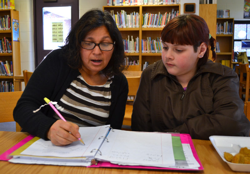 Lissette Griffin (left) works with Great Salt Bay Community School fifth-grader Catherine Shaw on Monday, Jan. 29. Every Monday and Tuesday, Griffin teaches Spanish to groups of students in the GSB library during their lunch and recess hour. (Maia Zewert photo)