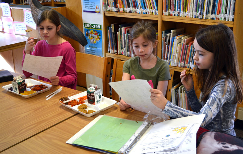 From left: Great Salt Bay Community School third-graders Emmaline Flewelling, Reese Nelson, and Penelope Boothby look over worksheets during a meeting of the Spanish club Monday, Jan. 29. (Maia Zewert photo)