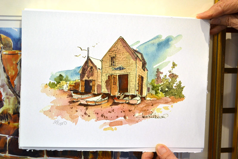 "Jan Kilburn holds a print of ""Fish Houses, Monhegan."" Kilburn likes to use pen and ink to outline buildings in her smaller pieces, such as this one. (Christine LaPado-Breglia photo)"