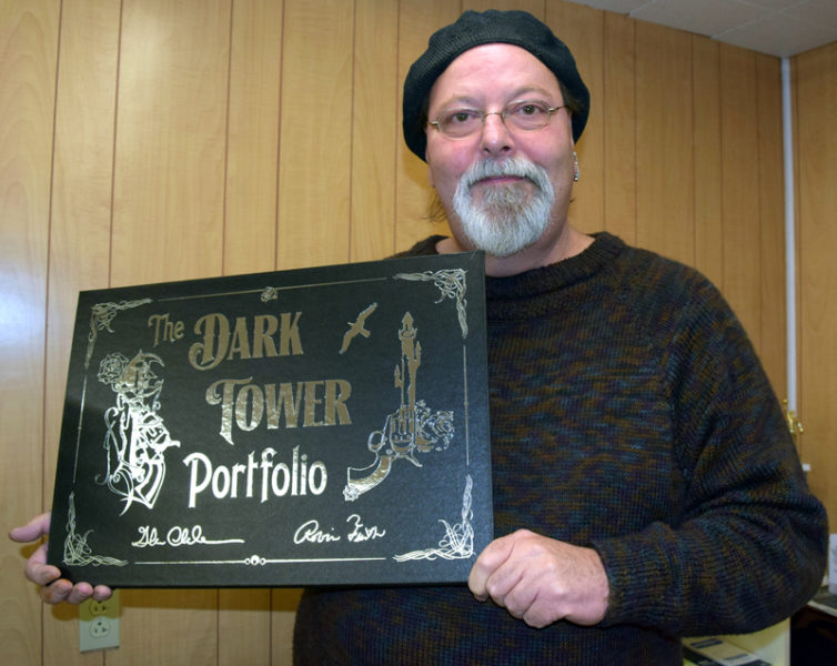 "Newcastle artist Glenn Chadbourne displays a copy of his most recent project, ""The Dark Tower Portfolio."" The collector's item features lithographs of nine original paintings by Chadbourne, including one for each of the eight books in ""The Dark Tower"" series by Stephen King. (J.W. Oliver photo)"
