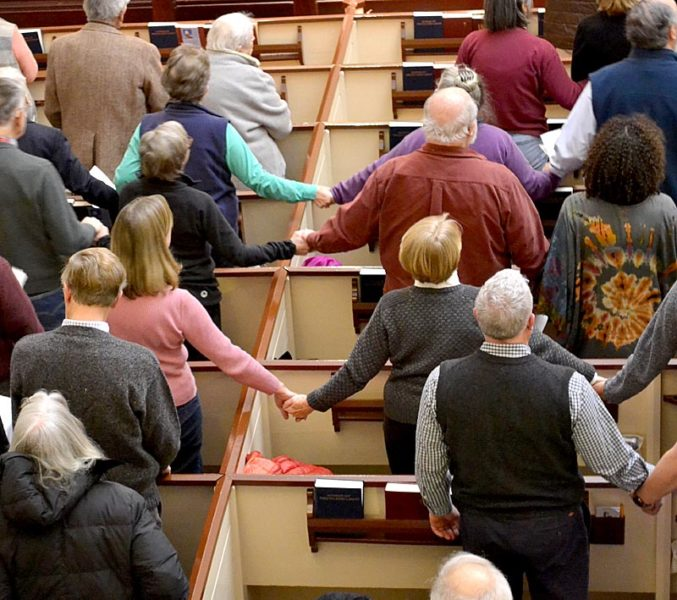 """Attendees of a Martin Luther King Jr. Day event at The Second Congregational Church in Newcastle hold hands while singing """"We Shall Overcome."""" (Abigail Adams photo)"""