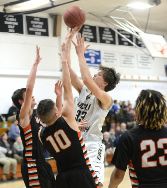 Cody Tozier shoots over a pair of Winslow defenders. (Paula Roberts photo)