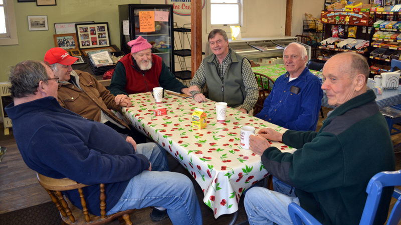 From left: Raymond Joslyn, Walter Shiappini, Larry Wilkes, Dan Joslyn, Merle West, and David Sutter solve the world's problems at The Alna Store on Monday, Feb. 27. Their work will continue under the new ownership, they said. (Abigail Adams photo)