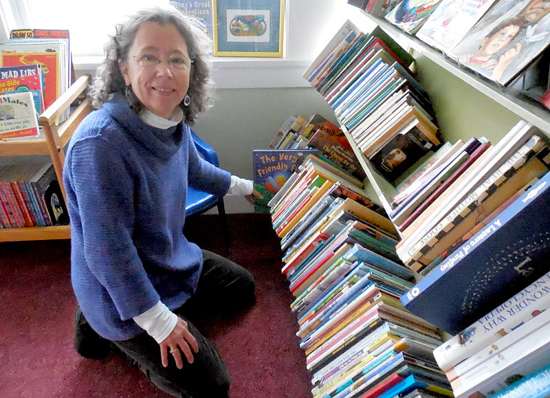 Rosie Bensen, co-manager of the Skidompha Secondhand Book Shop in Damariscotta, shelves books in the children's section of the newly relocated book shop, which is set to open Wednesday, Feb. 1. (Christine LaPado-Breglia photo)