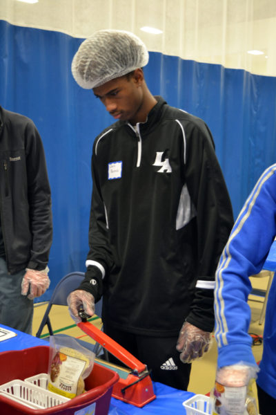 Lincoln Academy student Chris Dennis learns to heat-seal bags of dried macaroni noodles for distribution to local food pantries. (Christine LaPado-Breglia photo)