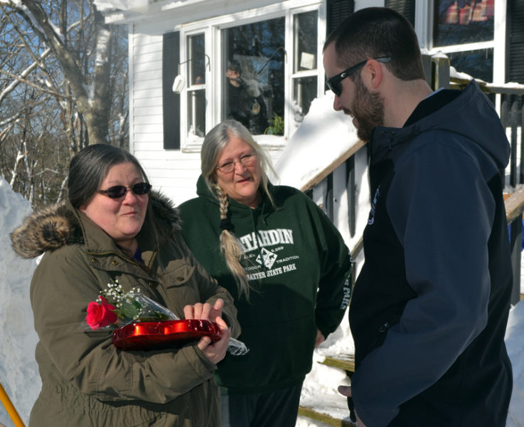 Damariscotta resident Georgia Woodman (left) thanks Matt Poole, of Colby & Gale Inc., for his delivery of flowers and chocolates as her sister, Lori Storer, looks on. On Valentine's Day, Colby & Gale surprised some of its customers with a free refill of their oil tank. (Maia Zewert photo)