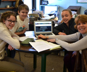 From left: Marina McManus, Andrew Lyndaker, Caitlin Cass, and Anne Plummer chat about the new Great Salt Bay Community School Online Gallery of Arts and Literature in Plummer's writing classroom. Plummer oversees the project, which McManus, Lyndaker, and Cass are thrilled to be involved with. (Christine LaPado-Breglia photo)