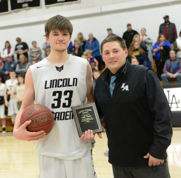 Lincoln Academy boys basketball coach Ryan Ball presented senior Cody Tozier with the game ball and a plaque in honor of his scoring his 1,000th career point on Feb. 2. (Paula Roberts photo)