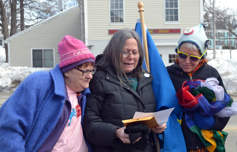 "Daphne Lehava Stern (center) reads ""The New Colossus,"" a poem writen by Emma Lazarus in 1883 for the construction of the Statue of Liberty's pedestal, as Eleanor Cade Busby (left) and Sharon Sandstrum look on. (Maia Zewert photo)"