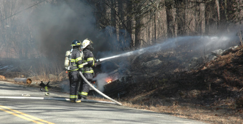 Firefighters work to prevent a car fire from spreading to the nearby woods on South Clary Road in Jefferson. (Alexander Violo photo)