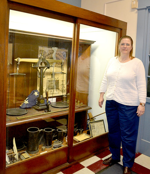 Lincoln County Administrator Carrie Kipfer points out a display cabinet of historic memorabilia at the courthouse. The cabinet will move to another location in the courthouse to make room for the relocation of the registry of deeds. (Charlotte Boynton photo)