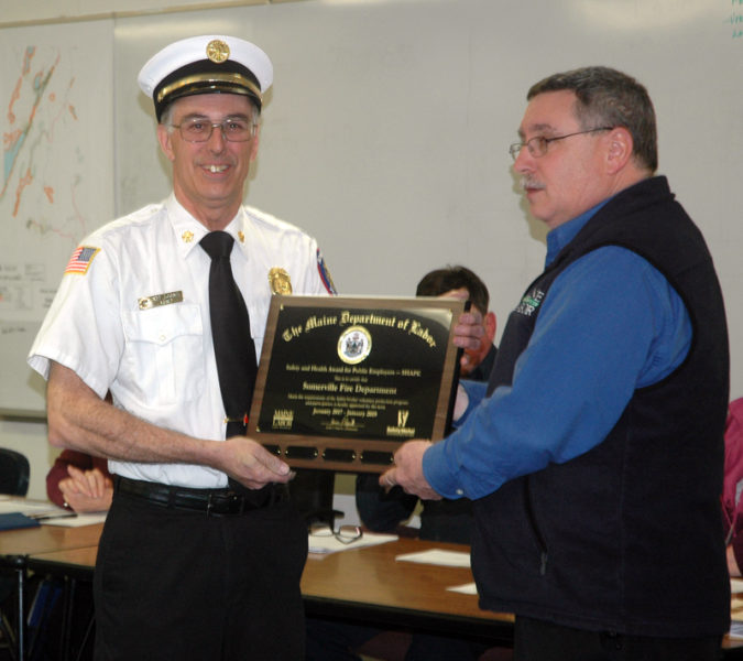 Somerville Fire Chief Mike Dostie accepts the Safety and Health Award for Public Employers from Michael LaPlante, of the Maine Department of Labor, at the Somerville town office Wednesday, March 1. (Alexander Violo photo)