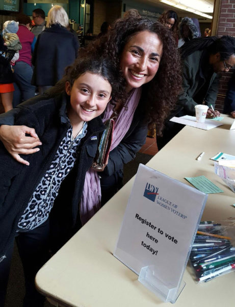 Vero Poblete-Howell, with her daughter, Sofia, registers to vote outside the naturalization ceremony at the University of Southern Maine in Portland. Her desire to vote was a major factor in her decision to pursue U.S. citizenship. (Photo courtesy Lisa Swain)