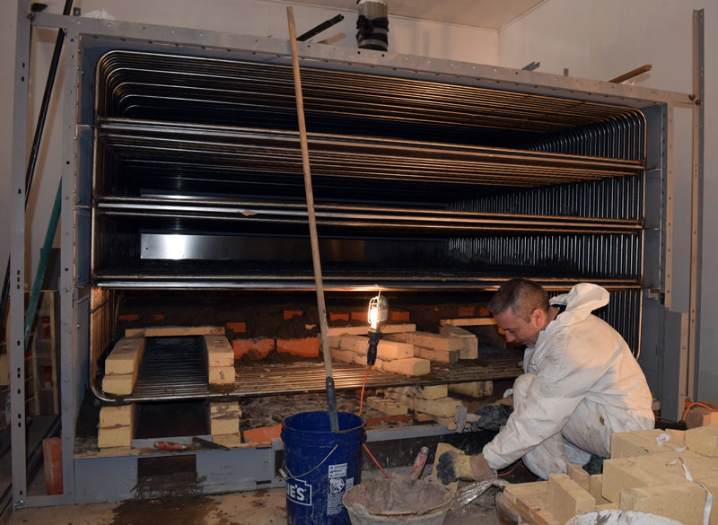 Norbert Creutzer works on the masonry for the new oven at Borealis Breads in Waldoboro on Friday, March 3. Creutzer works for the French manufacturer and traveled to Waldoboro to assemble the oven, a job that includes electrical work, masonry, and welding. (J.W. Oliver photo)