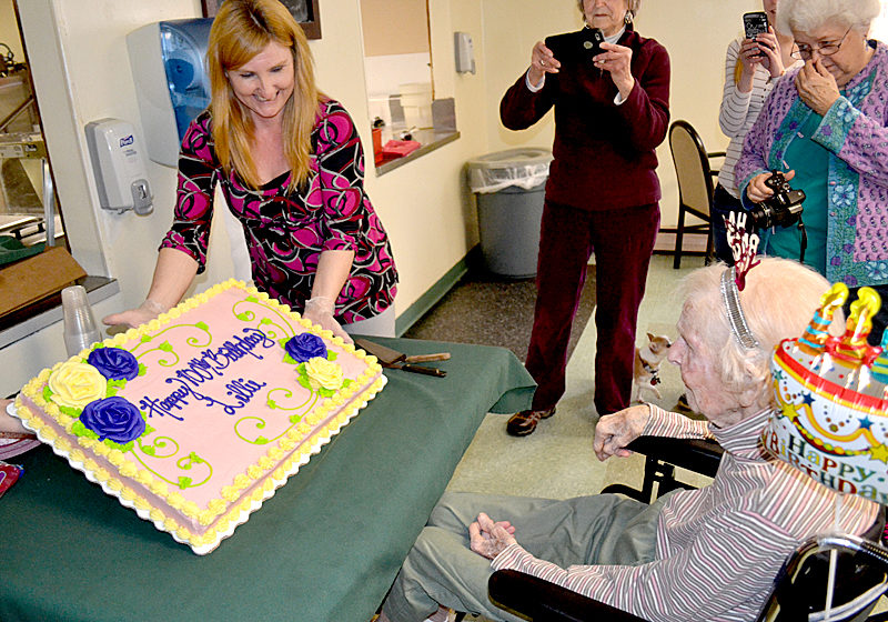 Country Manor Nursing Home Activities Director Tammy Brann shows Lillie Weissenberger her 100th birthday cake Monday, March 27. (Abigail Adams photo)