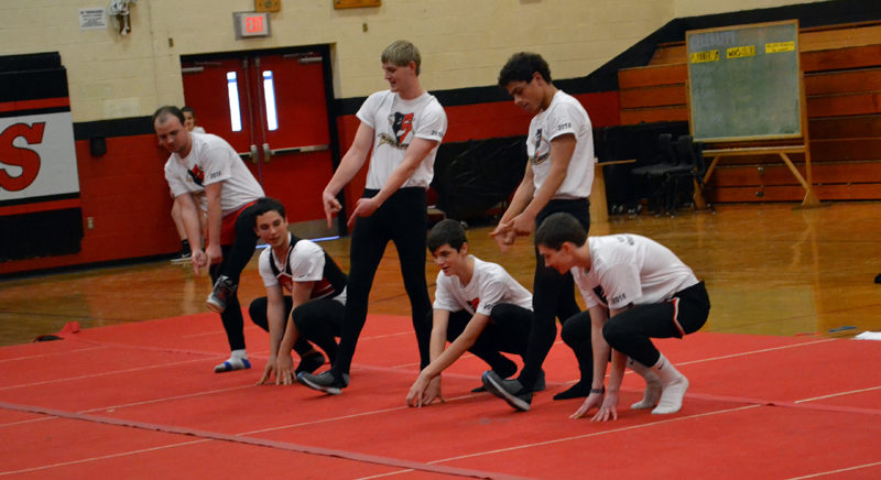 """From left: """"Juxtaposing Juniors"""" Trinin Jeffrey, David Fairfield, Nick Simmons, Jessie Perkins, Sam Strozier, and Max Sampson perform a choreographed routine complete with props and costume changes at Wiscasset high school's winter carnival. (Abigail Adams photo)"""