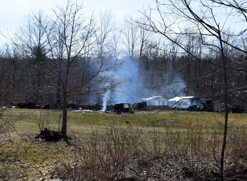The remains of a building smolder on Pension Ridge Road in Boothbay the morning of Saturday, April 15. (J.W. Oliver photo)