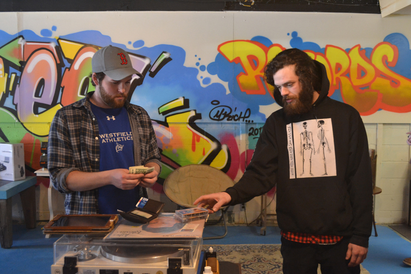 Jeffrey Lamb (left) purchases cassette tapes from Reel to Reel Music owner Zach Rankin on Monday, April 10. The new store in the Elm Street Plaza, 40 Elm St., Damariscotta, opened for business Saturday, April 8. (Maia Zewert photo)