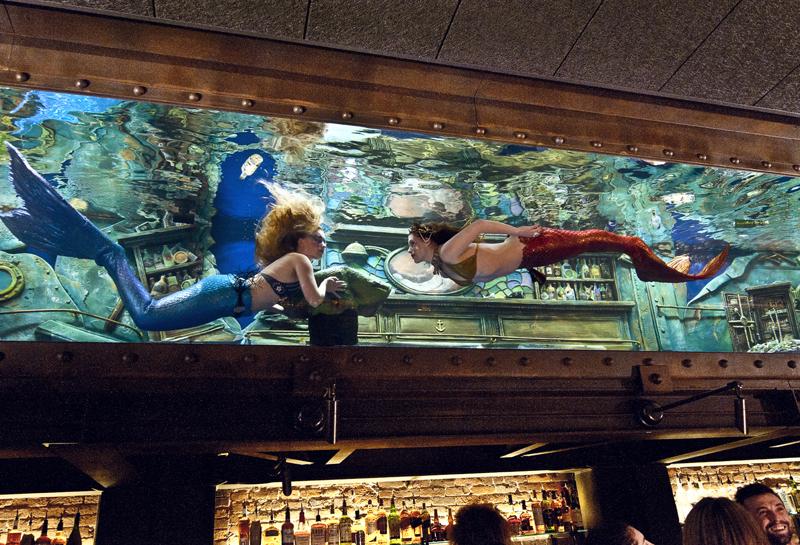 """Mermaids"" swim through an aquarium at the Dive Bar in Sacramento, Calif. Tenji Aquarium Design + Build, of Newcastle, Maine and Pacific Grove, Calif., designed and built the 7,500-gallon saltwater aquarium. (Photo courtesy Juan Ayora Photography)"