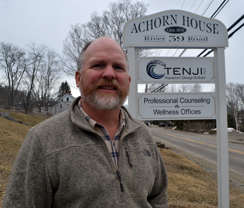 """Tenji Aquarium Design + Build co-owner Edward """"Ed"""" Seidel stands in front of the company's sign for its East Coast office at 39 River Road in Newcastle. (Maia Zewert photo)"""
