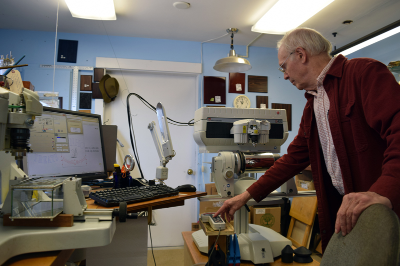 John Day demonstrates some of the equipment at Emporium Engraving in Newcastle on Friday, April 14. (J.W. Oliver photo)
