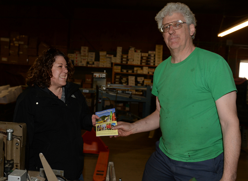 Damariscotta Region Chamber of Commerce Executive Director Stephanie Gallagher picks up the first Damariscotta Region Chamber of Commerce guide from Chris Roberts, of Lincoln County Publishing Co., on Friday, April 14. (Paula Roberts photo)