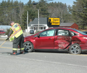 A member of the Waldoboro Fire Department sweeps debris out of the road at the scene of a three-car collision on Route 1 the morning of Monday, April 10. (Alexander Violo photo)