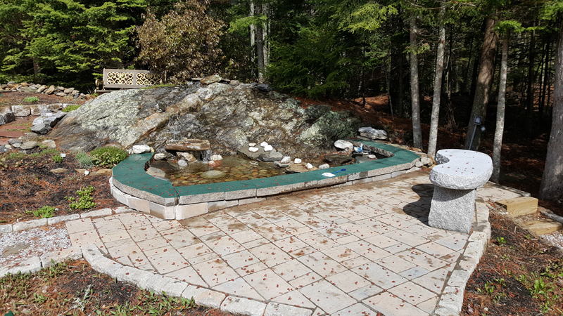 A patio with a water feature incorporating natural ledge on a property in Boothbay, designed and built by C.J. Turner. The water feature uses a reservoir and a pump to recirculate the water. (Photo courtesy C.J. Turner)